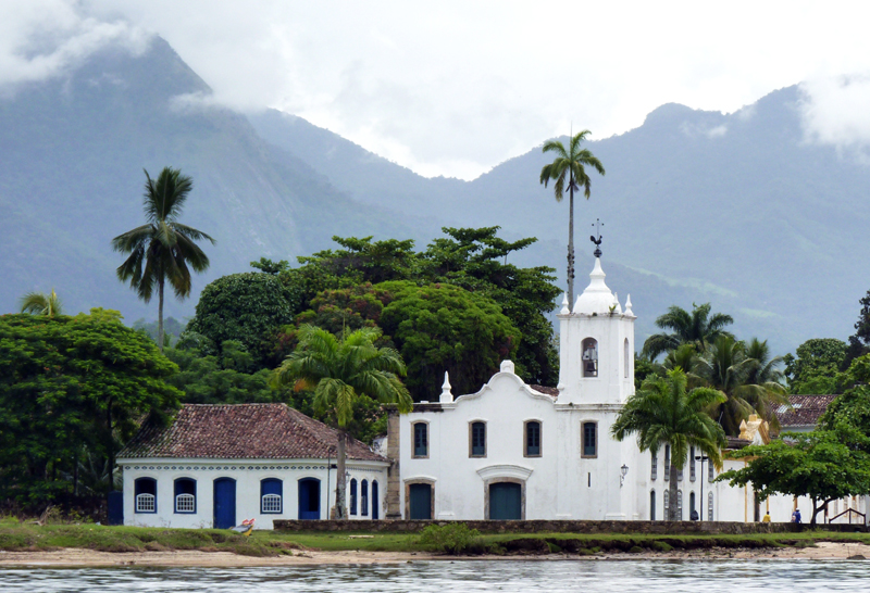 Paraty's whitewashed, terracotta tile-roofed buildings are framed by the soaring, jungle-clad mountains fringing the coast.